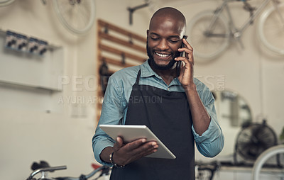 Buy stock photo Shot of a handsome young man standing alone in his bicycle shop and using technology
