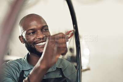 Buy stock photo Shot of a handsome young man standing alone in his shop and repairing a bicycle wheel