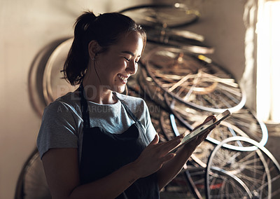 Buy stock photo Shot of a young woman using a digital tablet and working at a bicycle repair shop