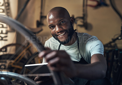 Buy stock photo Portrait of a young man holding a digital tablet working at a bicycle repair shop