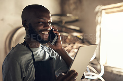 Buy stock photo Shot of a young man talking on a cellphone and browsing on a digital tablet while working at a bicycle repair shop
