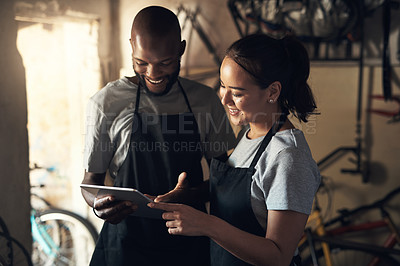Buy stock photo Shot of two young people browsing on a digital tablet while working at a bicycle repair shop