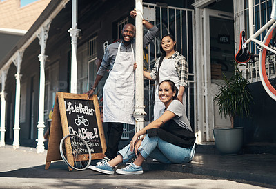 Buy stock photo Portrait of three young workers sitting outside of their bicycle repair shop