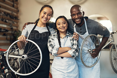 Buy stock photo Portrait of three young workers at a bicycle repair shop