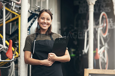 Buy stock photo Shot of an attractive young woman standing alone outside her bicycle shop and holding a clipboard
