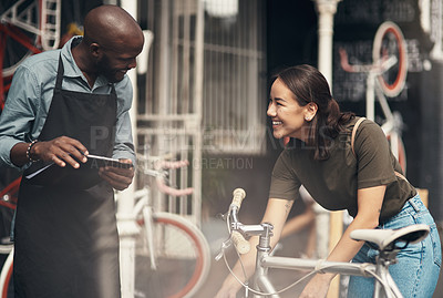 Buy stock photo Shot of a handsome young man standing outside his bicycle shop and assisting a customer