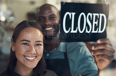 Buy stock photo Shot of two young colleagues standing together and turning the sign on the door to their bicycle shop