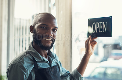 Buy stock photo Shot of a handsome young man standing and turning the sign on the door to his bicycle shop