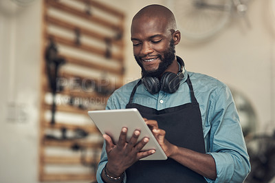 Buy stock photo Shot of a handsome young man standing alone in his bicycle shop and using a digital tablet