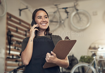 Buy stock photo Shot of an attractive young woman standing alone in her bicycle shop and using her cellphone while holding a clipboard