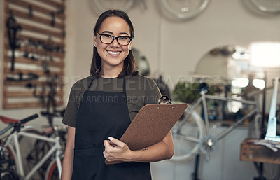 Buy stock photo Shot of an attractive young woman standing alone in her bicycle shop and holding a clipboard