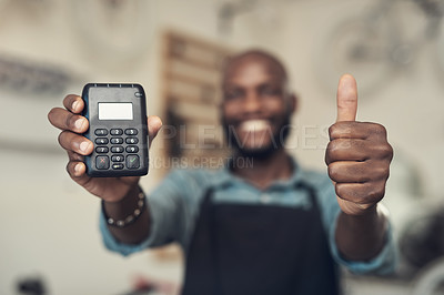 Buy stock photo Shot of an unrecognizable man standing in his shop and holding a card machine while doing a thumbs up gesture