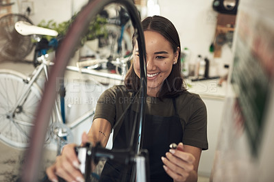 Buy stock photo Shot of an attractive young woman standing alone in her shop and repairing a bicycle wheel