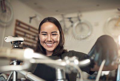 Buy stock photo Shot of an attractive young woman standing alone in her shop and repairing a bicycle