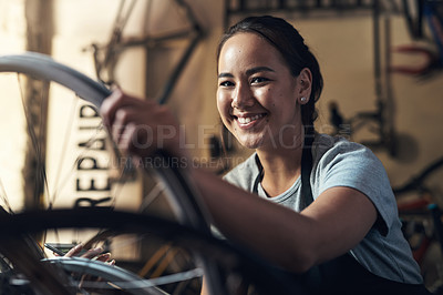 Buy stock photo Portrait of a young woman looking extremely pleased while holding a cellphone and fixing a bike at a bicycle repair shop