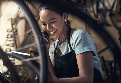 Buy stock photo Shot of a young happy young woman talking on a cellphone and using a digital tablet while fixing a bike at a bicycle repair shop
