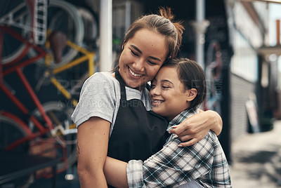 Buy stock photo Shot of two young female colleagues sharing a hug outside a bicycle repair shop