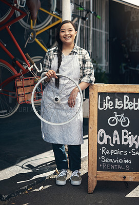 Buy stock photo Portrait of a young woman holding a bicycle wheel outside of a bicycle repair shop