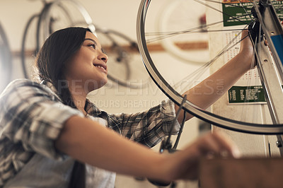 Buy stock photo Shot of a young woman fixing a bike at a bicycle repair shop