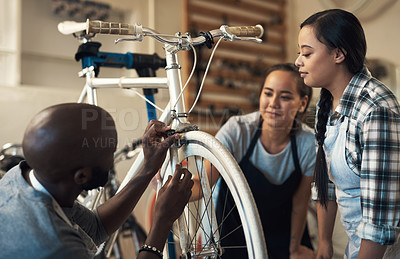 Buy stock photo Shot of three colleagues working together to fix a bike at a bicycle store