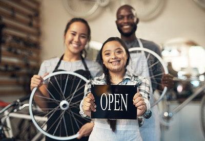 Buy stock photo Portrait of three workers standing and holding onto a bike while one displays an open sign at work