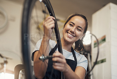 Buy stock photo Portrait of a young woman holding a bicycle wheel up at work