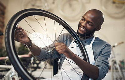 Buy stock photo Shot of a young man fixing a wheel at a bicycle repair shop