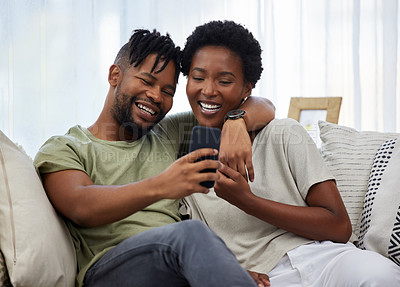 Buy stock photo Shot of a young couple taking a selfie while sitting on the couch at home