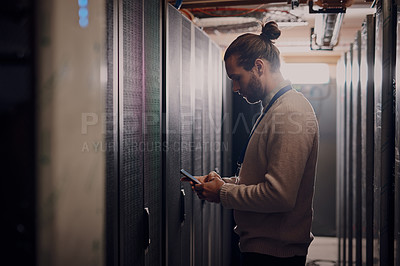 Buy stock photo Side shot of a young attractive man using his cellphone while working in a server room