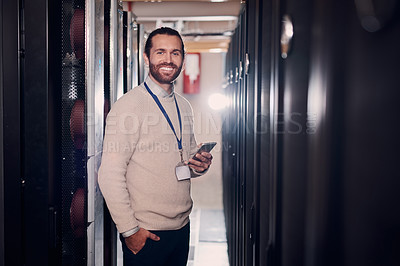 Buy stock photo Portrait of an attractive man holding a cellphone while working in a server room