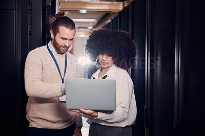 Buy stock photo Shot of two young workers using a laptop in a server room