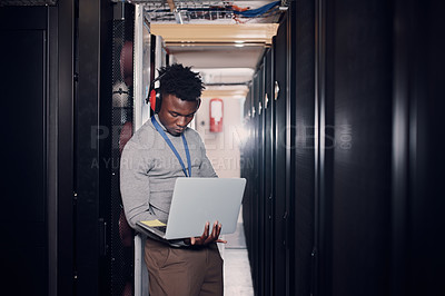 Buy stock photo Shot of an attractive young man using a laptop at work in a server room