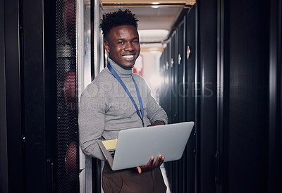 Buy stock photo Portrait of a young handsome man using a laptop at work in a server room