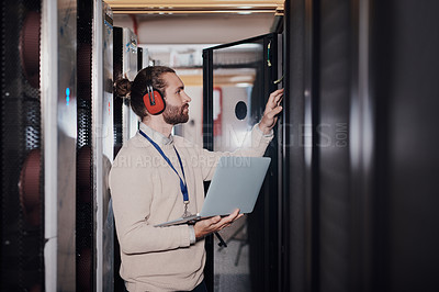 Buy stock photo Shot of a young handsome man wearing headphones and using a laptop at work in a server room
