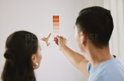 Buy stock photo Shot of an unrecognizable couple standing together and planning the interior design of their new home