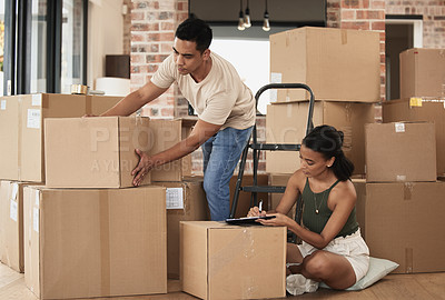 Buy stock photo Shot of a young couple packing up to move in a room at home