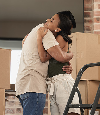 Buy stock photo Shot of a young couple hugging in to their new home