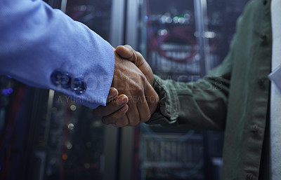 Buy stock photo Cropped shot of two unrecognizable male IT support agents shaking hands in a dark network server room