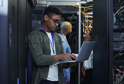 Buy stock photo Cropped shot of two male IT support agents working together in a dark network server room