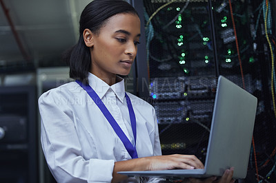 Buy stock photo Cropped shot of an attractive female IT support agent working in a dark network server room