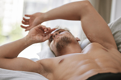Buy stock photo Cropped shot of a handsome and muscular young man looking thoughtful while lying in his bed at home