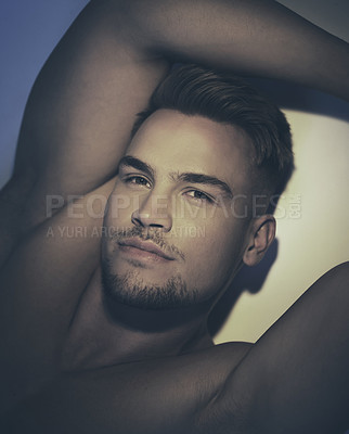 Buy stock photo Shot of a handsome young man with no shirt on laying in the shadows