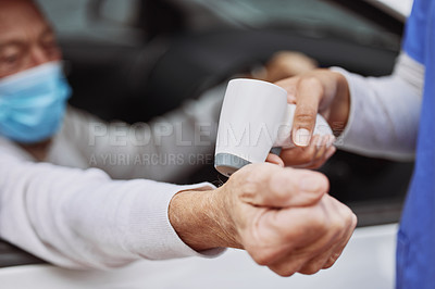 Buy stock photo Shot of an unrecognizable healthcare worker taking a patient's temperature at a drive through vaccination site
