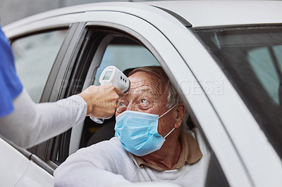 Buy stock photo Shot of a senior man getting his temperature taken at a drive through vaccination site