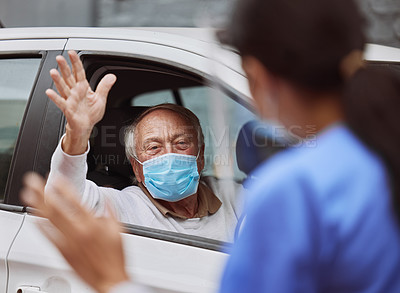 Buy stock photo Shot of a healthcare worker waving at a patient at a drive through vaccination site