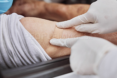 Buy stock photo Shot of an unrecognizable healthcare worker applying a band-aid to a patient's arm at a drive through vaccination site