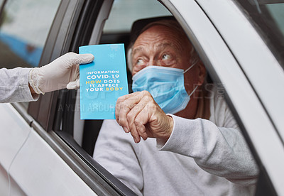 Buy stock photo Shot of a senior man taking a pamphlet from a healthcare worker at a drive through vaccination site