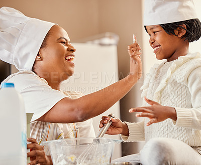 Buy stock photo Shot of a mother and her daughter baking in the kitchen at home