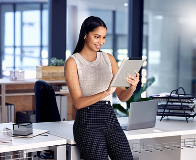 Buy stock photo Shot of a young businesswoman using her digital tablet at work