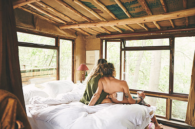 Buy stock photo Shot of a young couple relaxing on a bed while on holiday in a cabin